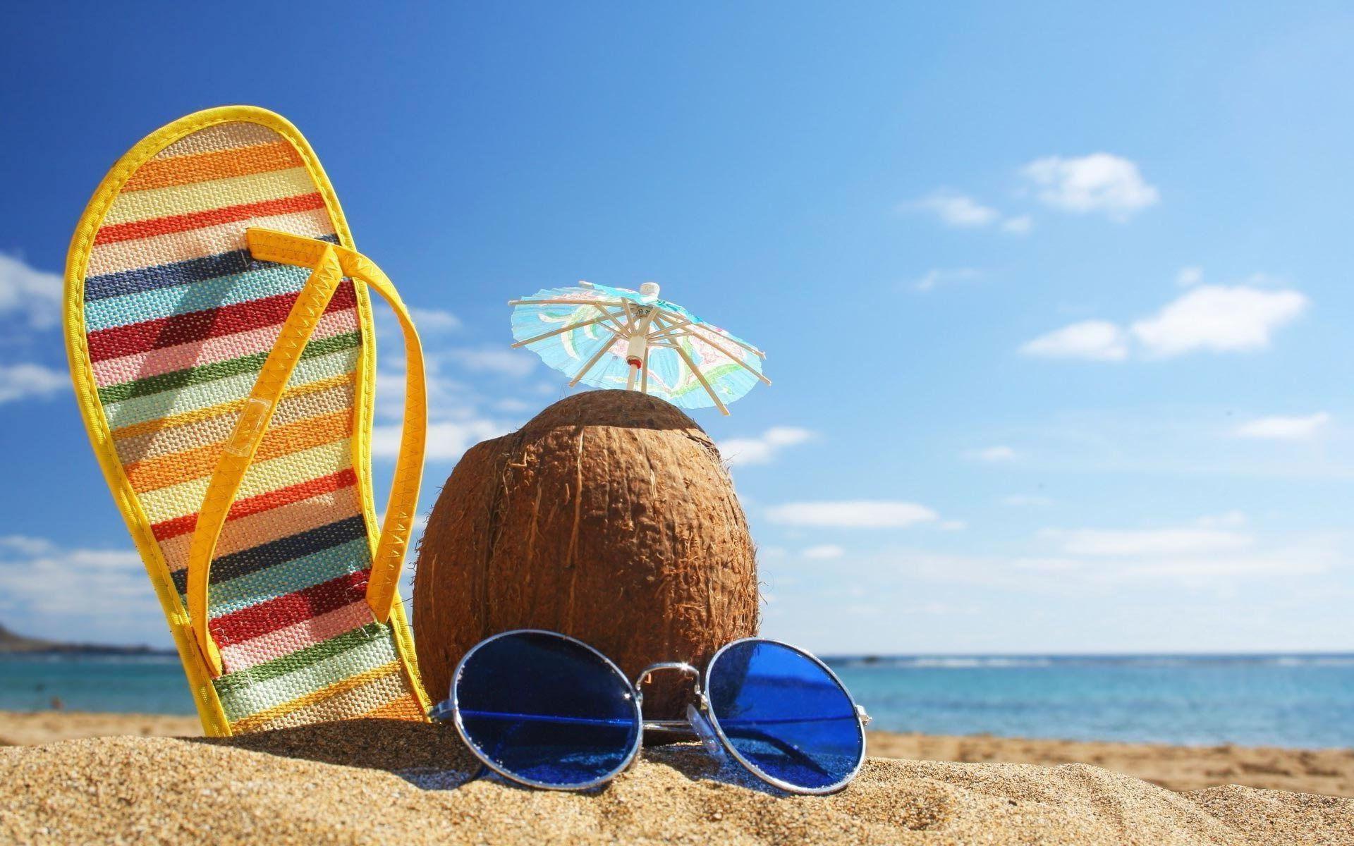 download wallpaper: Een zandstrand met een zonnebril, slippers en een kokosnoot wallpaper